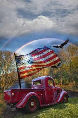 red pickup truck flaying american flag with eagle soaring in blue skies